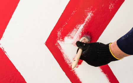 The hand in the black glove holds the brush. On the wall with red paint draws an arrow