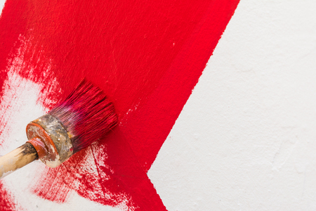 paintcan: Staining the red strip on the wall with a round brush Stock Photo