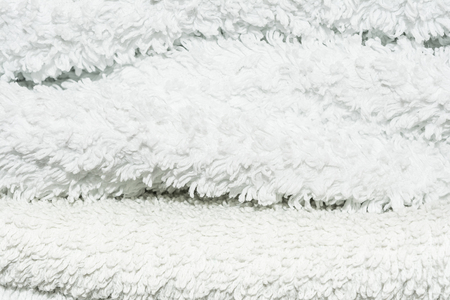 texture of white terry cloth, unevenly stacked towels, abstract background