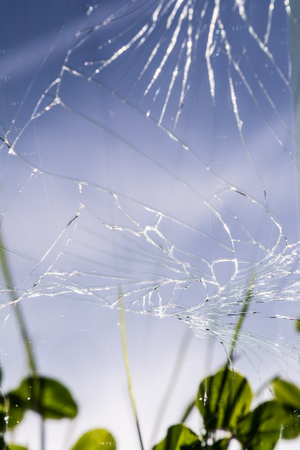 many cracks on the mobile phone screen, selective focus, reflection on the glass of green grass, blue sky, abstract background