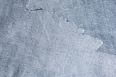 hole: shreds of denim fabric, unevenly cut jeans, abstract background