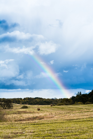 autumn landscape with cloudy weather, large rainy clouds over a chamfered yellow field, the rainbow is in the sky, nature background Stock Photo