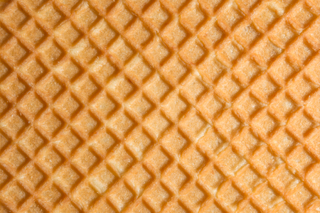 Relief texture of the surface of a cookie or favi, close-up abstract background