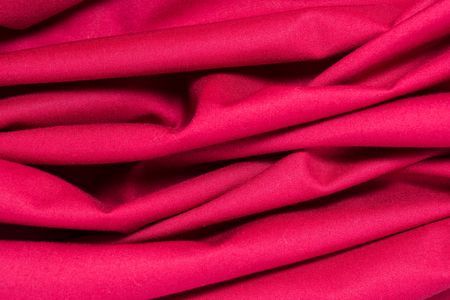 texture of red cotton fabric with arbitrary bends and wave, close-up abstract background