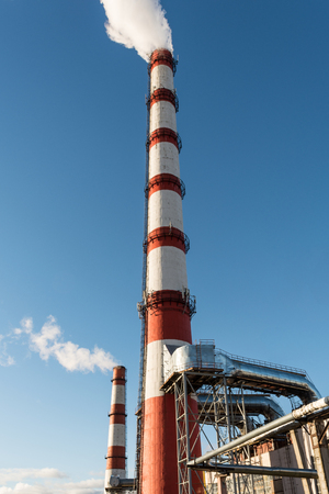 combined heat and power plant, from the pipe goes white smoke against a background of pure blue sky, industry background Banco de Imagens - 93047895