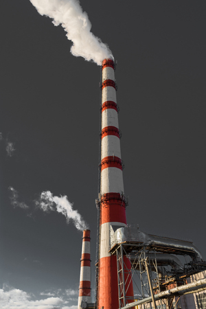 combined heat and power plant, from the pipe goes white smoke against a background of pure gray sky, industry background