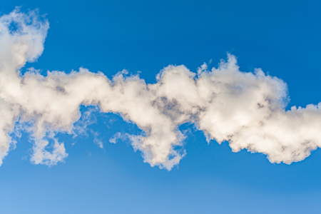 thick white smoke on a background of blue sky, abstract background
