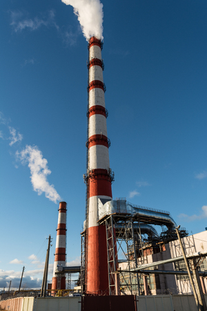 combined heat and power plant, from the pipe goes white smoke against a background of pure blue sky, industry background Banco de Imagens