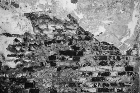 gray texture of an old wall of an ancient building with a ruined plaster layer and cracked bricks, abstract background