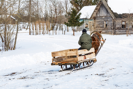 a villager in a village goes in a makeshift sleigh and runs a horse, a clear winter day