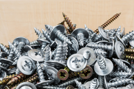a group of silvery and golden self-tapping screws is arbitrarily positioned on a wooden surface, selective focus, close-up abstract background
