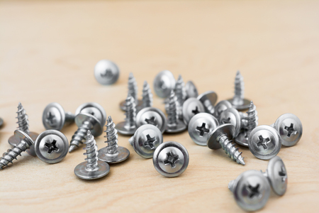 a group of silvery self-tapping screws is arbitrarily positioned on a wooden surface, selective focus, close-up abstract background