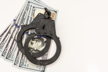 black metal handcuffs lie on 100 dollar bills on a white background, conceptual abstract background Stock Photo