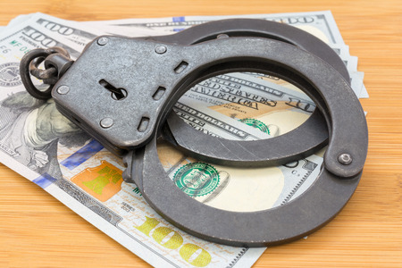 black metal handcuffs lying on the 100 dollars banknotes on a wooden background, concept abstract background