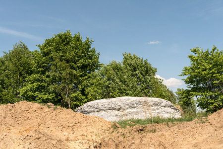 large gray stone is located on a sandy hill, trees with green foliage on a background of blue sky, nature abstract background