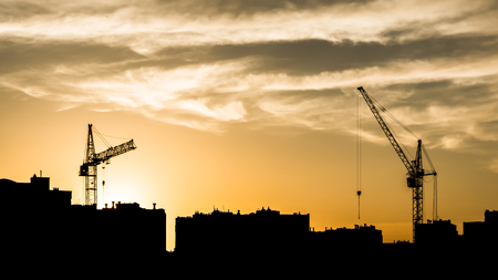 silhouettes of two tower cranes and houses during sunset, sunset with an orange sky in the city