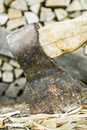 old ax is stuck in a stump against the backdrop of a woodpile, selective focus, close-up abstract background Banco de Imagens