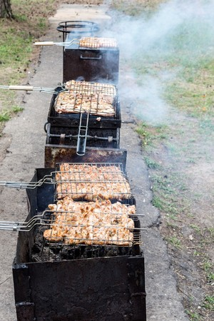 three braziers for cooking shish kebab, grill with meat, cooking at a picnic Foto de archivo