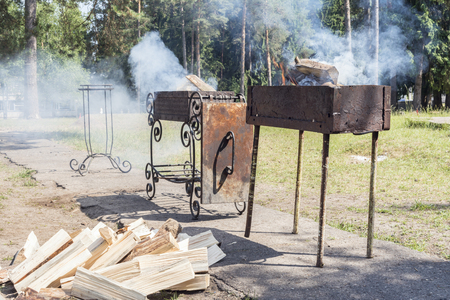 two braziers with burning firewood in the park area, lots of smoke during the ignition of the barbecue, a summer sunny day