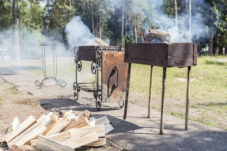 Dos braseros con leña en el área del parque, mucho humo durante el encendido de la barbacoa, un día soleado de verano Foto de archivo - 103859049