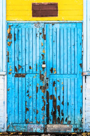 blue old wooden door with peeling paint and big damages, doorway in a yellow white abandoned building, antique architecture abstract background