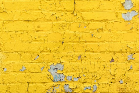 texture old brick wall painted yellow paint, peeling and crumbling paint on white bricks, architecture abstract background