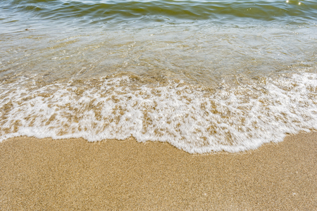 sea shoreline with waves, sandy beach on a clear sunny day, close-up nature abstract background 免版税图像