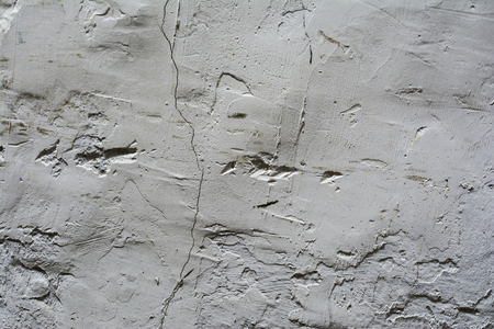 gray relief texture of an old wall with potholes and fissure, close-up architecture abstract background