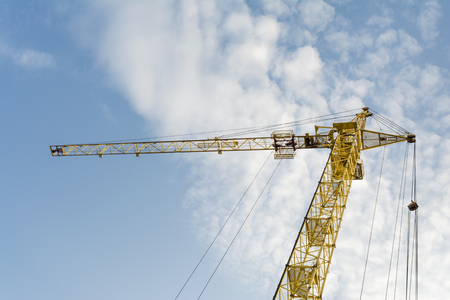 one yellow tower crane on a background of blue sky with clouds, industry abstract background