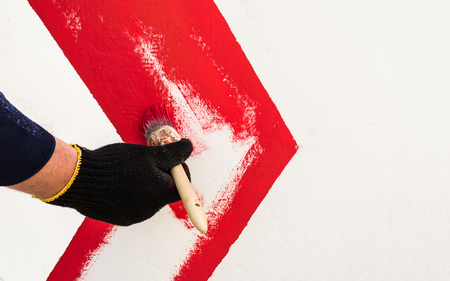 On the wall with red paint draws an arrow. The hand in the black glove holds the brush.