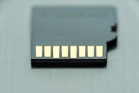 black micro sd card with gold contacts on a gray metallic surface, selective focus, macro Stok Fotoğraf