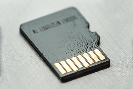 black micro sd card with gold contacts on a gray metallic surface, selective focus, macro 免版税图像