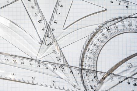 goniometro, triangolo e righello in plastica trasparente sullo sfondo di un quaderno in una gabbia Archivio Fotografico