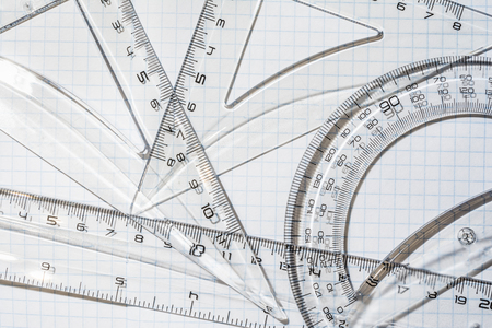 transparent plastic protractor, triangle and ruler on the background of a notebook in a cage