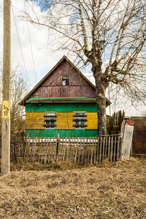 old wooden abandoned house, yellow green country house with boarded up windows, countryside in early spring