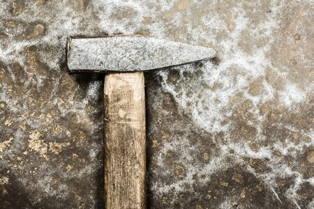 old hammer on rumpled shabby metal surface, close-up abstract background