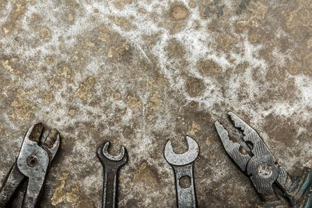 old worn tool on rumpled shabby metal surface, close-up abstract background Stock fotó