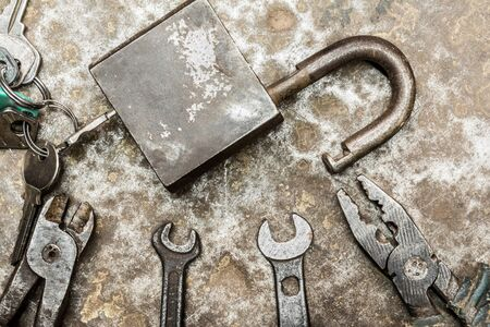 padlock and old worn tool on rumpled shabby metal surface, close-up abstract background Reklamní fotografie