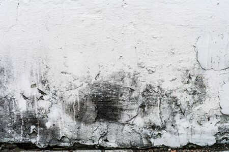 texture of an old wall with uneven cracked stucco, dirty surface of the exterior painted wall, architecture abstract background Imagens