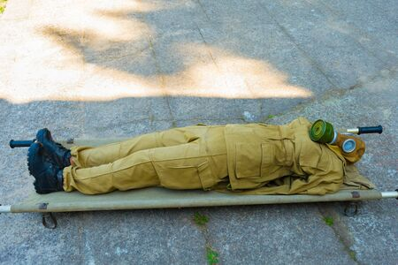 a model of a soldier in a gas mask lies on a military stretcher, chemical protection suits Stock Photo