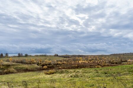 Green field and trees with yellow and orange foliage. Beautiful autumn landscape on a cloudy day with a cloudy sky. 写真素材