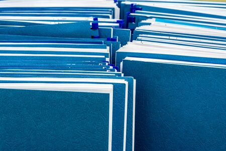 Two row of blue folders with documents in paper box, close-up paperwork abstract background, selective focus in the foreground