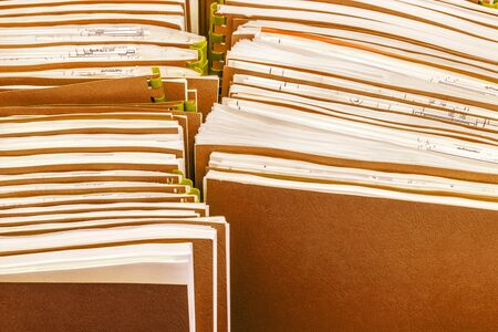 Two row of retro folders with documents in paper box, close-up paperwork abstract background, selective focus in the foreground