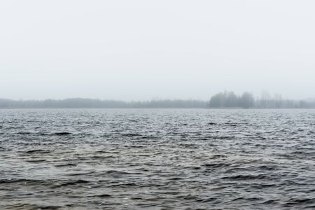 cold water surface in fog with barely visible blurred distant shore on the horizon, nature background