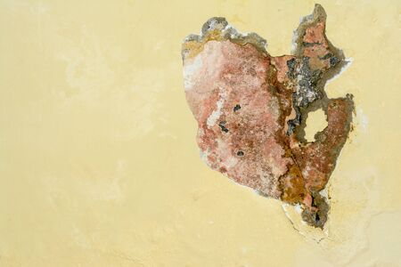 Chipping yellow plaster paint on white stone wall, close-up abstract background