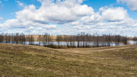Landscape of European plains with hills and lowlands, lake, meadows and forests. Blue sky with clouds over horizon. Nature in early spring Reklamní fotografie