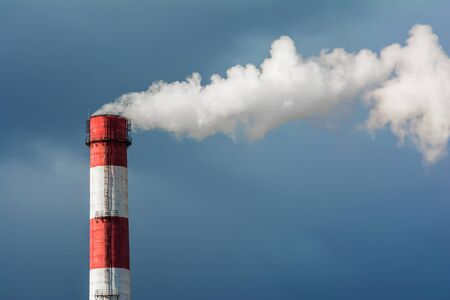 A smoking chimney in a blue sky. The emission of harmful gases into the atmosphere, greenhouse efekt. Air pollution, Close-up of one big smoking pipe.