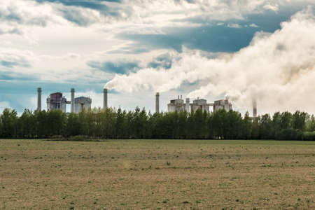 Industrial plant set in rural area spewing out big clouds of steam or smoke pollution against a blue sky with clouds Reklamní fotografie