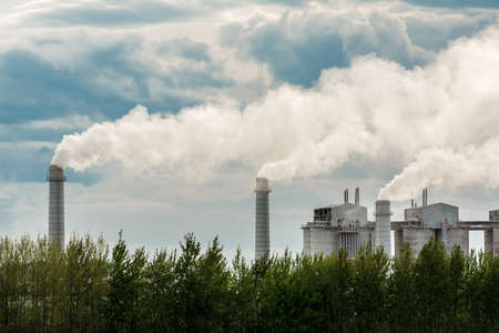 Industrial plant set in rural area spewing out big clouds of steam or smoke pollution against a blue sky with clouds