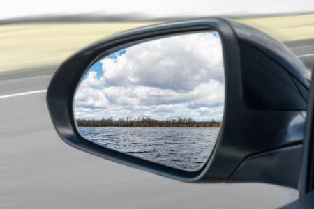 in the mirror of the car you can see a forest lake and large white clouds in autumn or spring Imagens